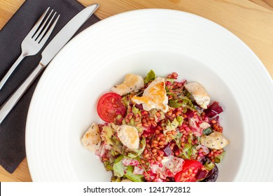 Hot chicken salad with einkorn, salad mix, red beetroot and cherry tomatoes.