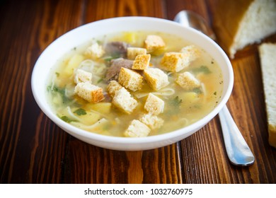 hot chicken soup with homemade noodles and croutons on a wooden table