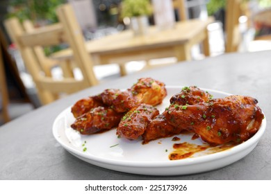 Hot chicken wings on a white ceramic dish.