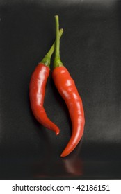 Hot chili peppers on a black ceramic plate. Selective focus.