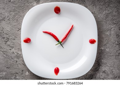 Hot chilli pepper on white plate with decor ketchup