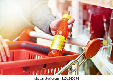 Hot chilli sauce in the hands of the buyer at the grocery store