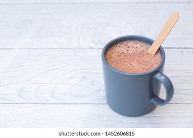 Hot chocolate in a blue-grey ceramic mug with wooden stirrer isolated on white painted wood. Space for text.