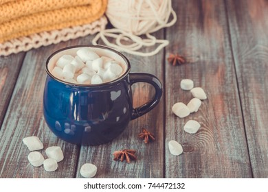 Hot chocolate or cacao in a blue mug with marshmallows on the table with wool.
