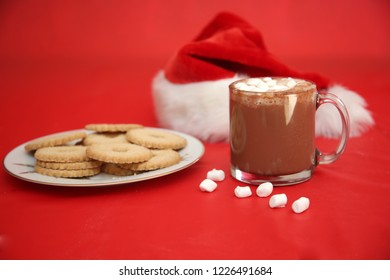 Hot Chocolate. Christmas Time Foods. Cocoa with mini marshmallows sugar cookies and a candy cane. On a red background with a santa hat.