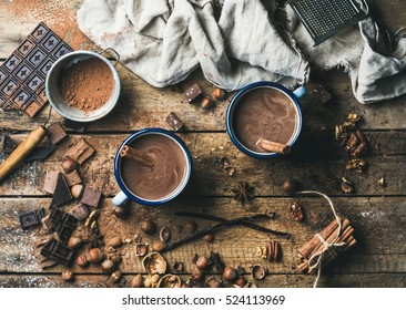 Hot chocolate with cinnamon sticks, anise, nuts and cocoa powder on rustic wooden background, top view, horizontal composition