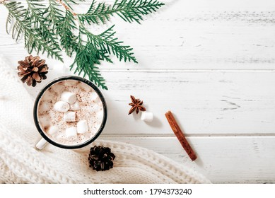 hot chocolate,  cocoa mug with marshmallows, white sweater, fir branches , cones, cinnamon sticks, star anise on a white wooden background, hot winter drink, place for inscription