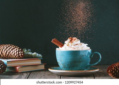 Hot chocolate with cream and cinnamon stick in a blue ceramic cup on a table with a books. The concept of winter or fall time.