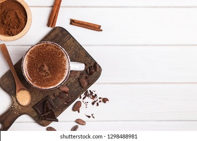Hot chocolate in the cup, cocoa beans and powder on the white wooden table, top view