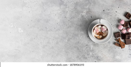 Hot chocolate cup with cream and marshmallow on large background. Traditional beverage for cold days concept. Copy space