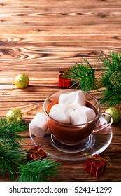 Hot chocolate in cup with marshmallows and fir on wooden table
