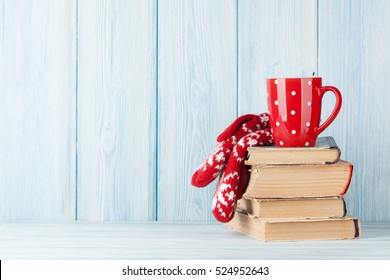 Hot chocolate cup and mittens over books. Christmas. View with copy space