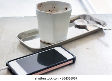 Hot chocolate cup and smart phone, stock photo
