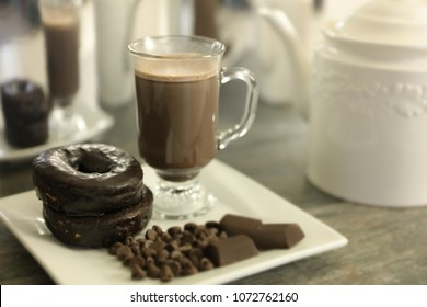 Hot chocolate, chocolate donuts, chocolate candy and a white pitcher.