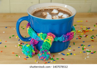 hot chocolate drink with colorful knit scarf tied around blue mug on wood table and sprinkles