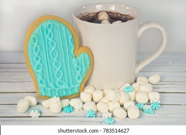 hot chocolate drink with mitten cookies and marshmallows on whitewashed wood