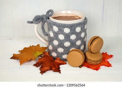 hot chocolate drink in mug with gray and white polka dot knitted sweater and macaroons on autumn leaves
