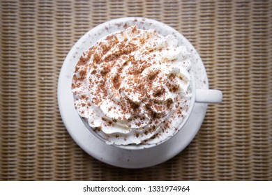 A hot chocolate drink with whipped cream and cinnamon