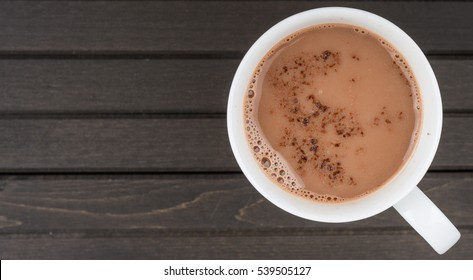 Hot chocolate drink in a white mug over wooden background