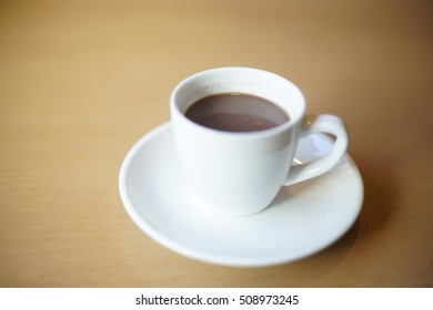Hot chocolate drinks in white cup on the wooden table.