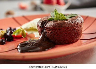Hot Chocolate Fondant with Mint Leaves and Berries on Terracotta Plate Close Up. Fresh Brownie Dessert with Melted Dark Cocoa Mousse. Small Chocolate Cake with Crunchy Rind and Mellow Filling