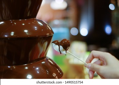 hot chocolate fondue fountain with a slice of fruits on a fork being dipped