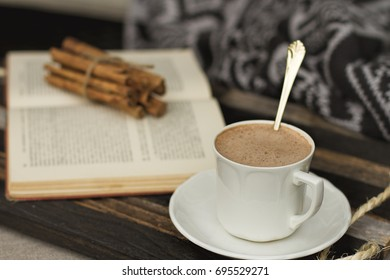Hot Chocolate and a good book on a wooden tray with cinnamon sticks and a cozy blanket.