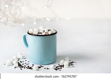 hot chocolate with marshmallow in a blue mug on a light background close-up