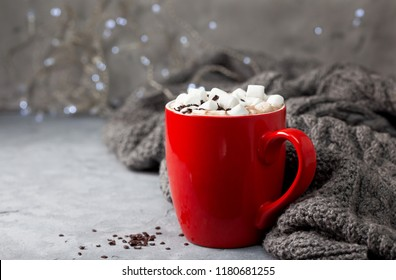 hot chocolate with marshmallow in a red mug on a gray stone background