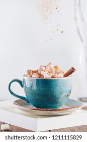 Hot chocolate with marshmallows and cinnamon stick in a blue ceramic cup on a table with a book. The concept of winter or fall time. Minimal scandinavian design.