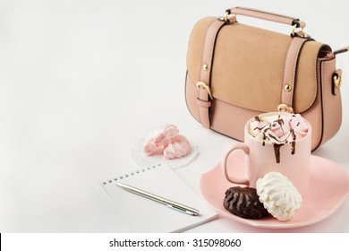 Hot chocolate with marshmallows, notepad and women's handbag on a white background. Selective focus.