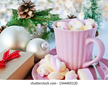 Hot chocolate with marshmallows in pink mug on Christmas table with gift on bokeh background.
