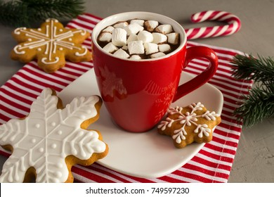 Hot chocolate with marshmallows in the red cup and Christmas cookies on the napkin