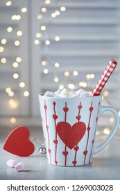 Hot chocolate with marshmallows, red heart on the cup, winter background with lights out of focus. Winter or Valentine's day background.