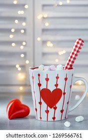 Hot chocolate with marshmallows, red heart on the cup, winter background with ceramic heart and lights out of focus. Winter or Valentine's day background.