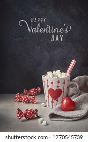 Hot chocolate with marshmallows, red heart on the cup, wrapped candy on the table. Valentine's day background with text greeting.