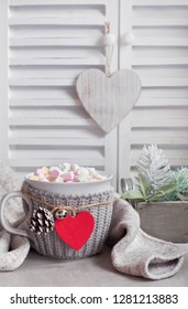 Hot chocolate with marshmallows, red heart on the cup on the table with winter decorations. Birthday or Valentine's day background.