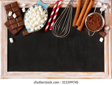 Hot chocolate mix on old chalk blackboard. Sweet marshmallow, chocolate bars, sugar, cocoa powder, cinnamon, and whisk for cooking winter holiday drink.