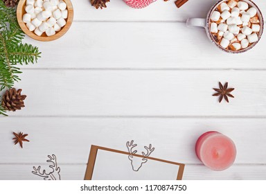 Hot chocolate and other Christmas accessories on the white table, arranged on the frame shape