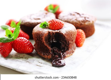 Hot chocolate pudding with fondant centre with strawberries, close-up