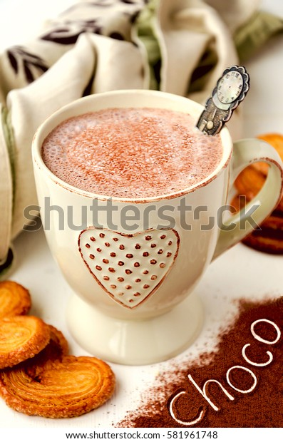 Hot chocolate with puff pastry swirl cookies and text cocoa on the cocoa powder