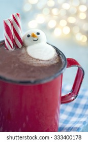 Hot chocolate in a rustic red mug with candy canes and a marshmallow snowman on blue vintage background and bokeh lights