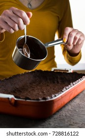 Hot chocolate in a saute pan and a spoon, dough in a baking dish