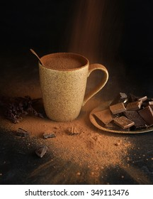 Hot chocolate with chocolate slices and chocolate powder on a dark background