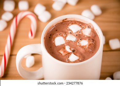 Hot Chocolate - This is a shot of a hot cup of hot chocolate with marshmallows and a candy cane setting nearby.
