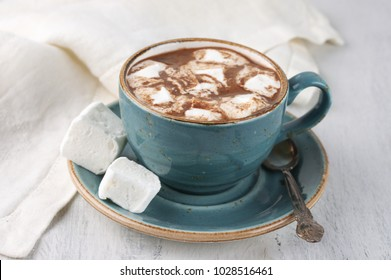 Hot chocolate with whipped cream and marshmallow in teal color cup on rustic white wooden table.