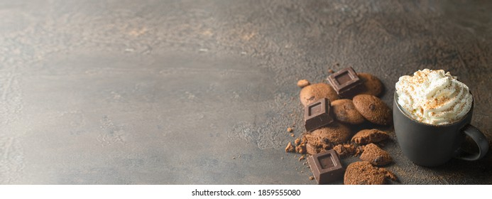 Hot chocolate with whipped cream , chocolate slices and cookies on  large concrete background for banner  with copy space.