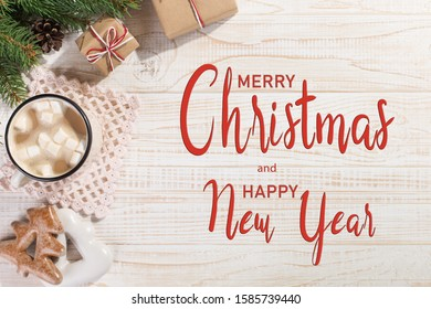 Hot Christmas drink with marshmallows in an iron mug and gingerbread cookies, on white table. New Year, holiday background, copy space.