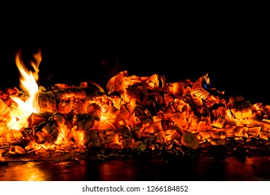 hot coals in the fireplace with tongues of flame on a black background