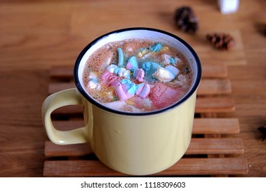 Hot cocoa drink with a multicolored marshmallow in a yellow cup.